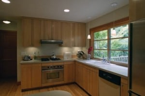 Spacious kitchen with window looking out on wooded beauty